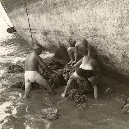Søfolk hjælper skib af grunden